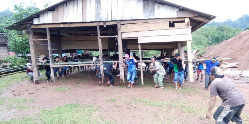 Warga kampung Rea, Lakahang Utama, bergotong-royong mengangkat rumah salah seorang warga, Senin, 12 September 2016. (Foto: Andi Arwin)