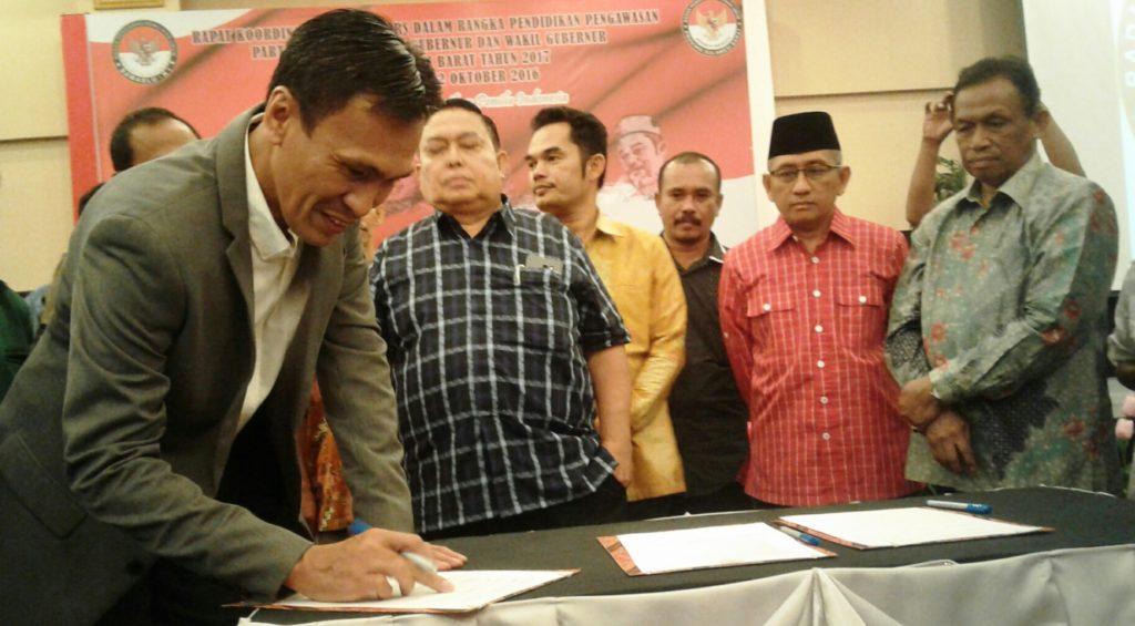 Ketua KPU Sulbar Usman Suhuriah (kiri) sedang menandatangani Fakta Integritas, Jumat malam, 21 Oktober 2016. (Foto: Risman Saputra)