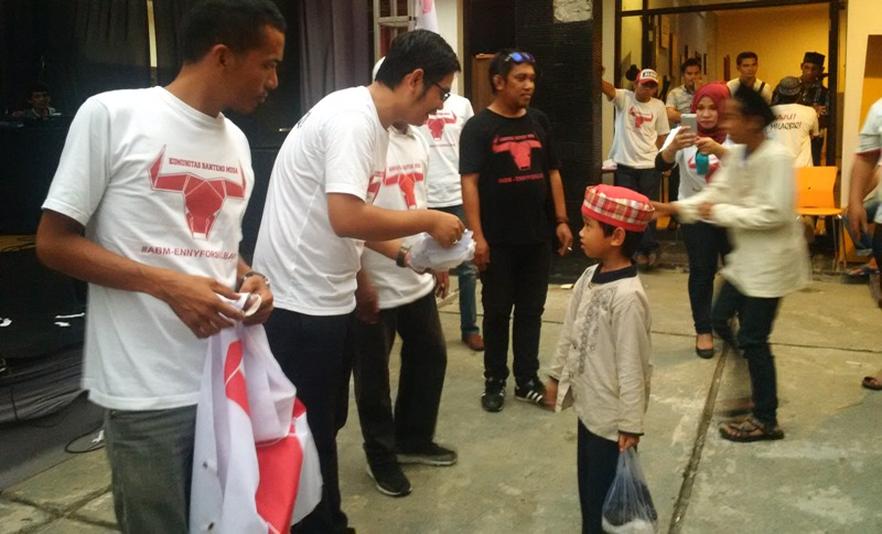 Anggota DPRD Sulbar dari PDI Perjuangan (Dapil Mamuju), Ahmad Istiqlal Ismail (kiri, menunduk) sedang meyerahkan bingkisan kepada salah seorang anak panti asuhan, Mamuju, 28 Oktober 2016. (Foto: Anhar Toribaras)