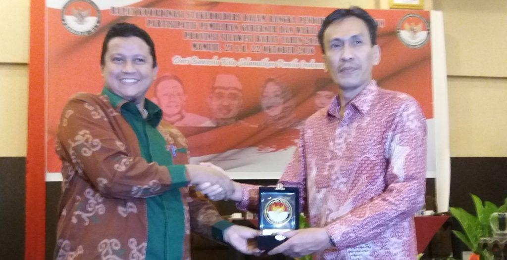 Ketua KPU Sulbar Usman Suhuriah (kanan) terima cendramata dari Ketua Bawaslu RI Prof. Dr. Muhammad (kiri), Jumat siang, 21 Oktober 2016. (Foto: Risman Saputra)