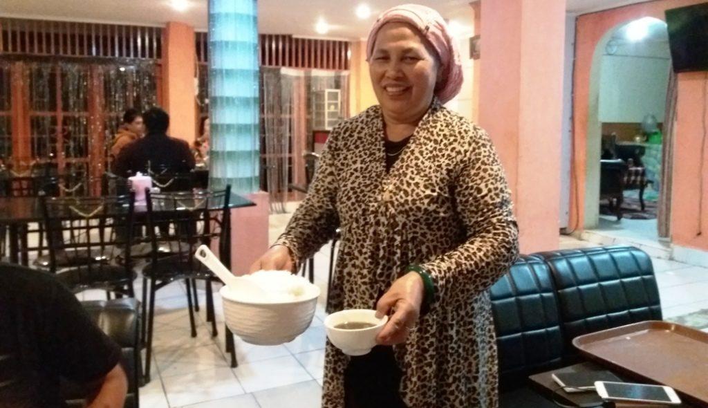 Hajjah Rafiah sedang melayani pengunjung Rumah Makan Dapoer Hj. Rafiah, Mamasa, Kamis malam, 8 September 2016. (Foto: Sarman Shd)